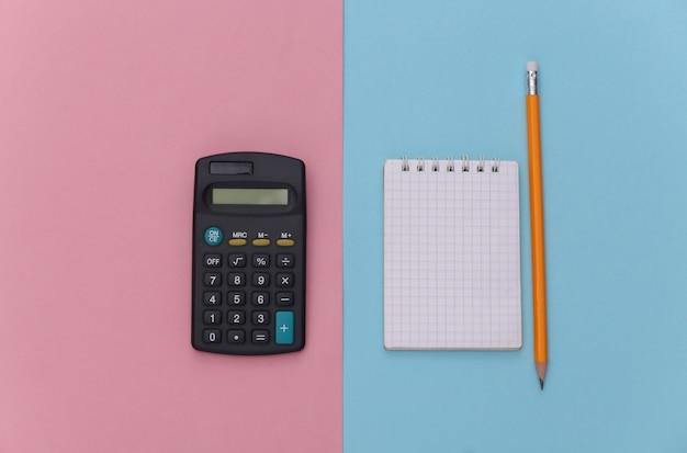 Notizbuch mit bleistift, taschenrechner auf rosa blauem pastellhintergrund. ansicht von oben