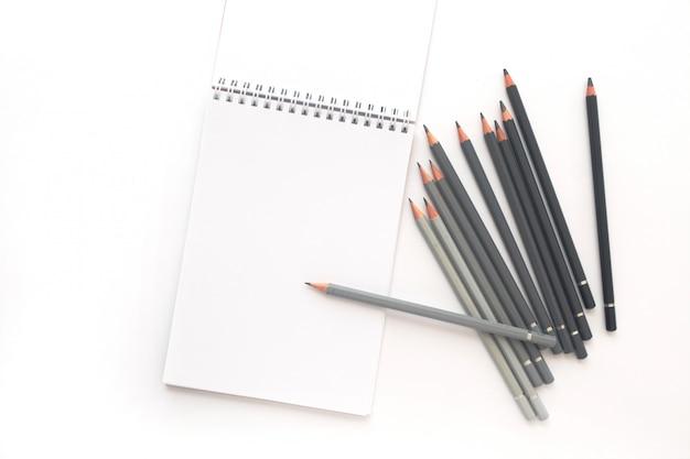 Notizbuch mit bleistiften auf weiß. ansicht von oben