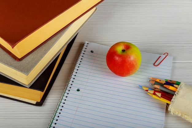 Notizbuch mit bleistiften, taschenrechner und verschiedenem schul- oder bürozubehör.