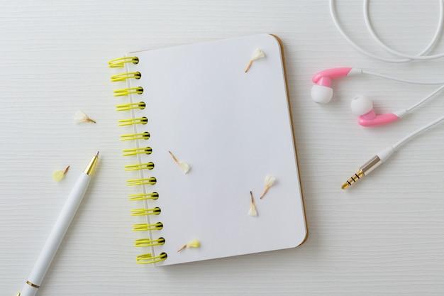 Notizbuch mit blumenkopfhörer und -stift