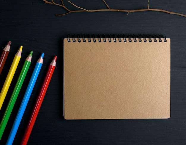 Notizbuch mit braunen seiten und mehrfarbigen hölzernen bleistiften