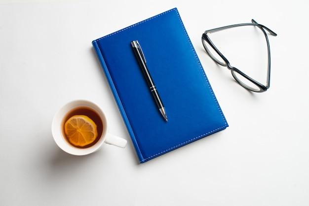 Notizbuch mit brille und stift, buch mit brille, blaues notizbuch mit brille, buch mit tasse tee