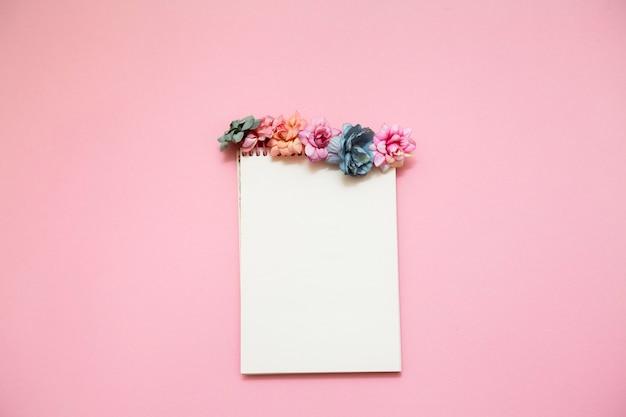 Notizbuch mit bunten blumen auf einer rosa oberfläche verziert.