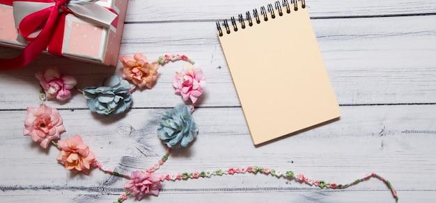 Notizbuch mit bunten blumen verziert in form eines herzens auf einer holzoberfläche