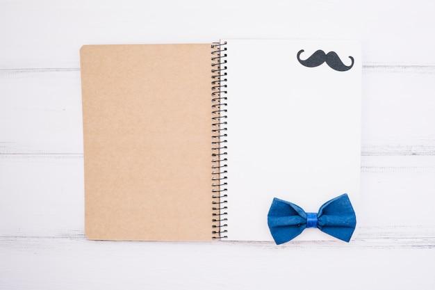Notizbuch mit dekorativem schnurrbart und fliege