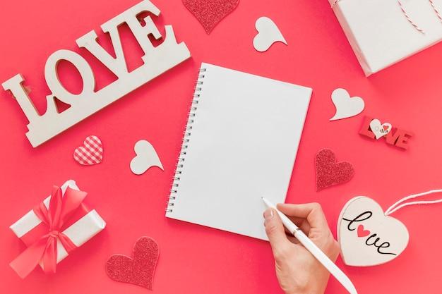 Notizbuch mit der hand und stift für valentinsgrüße