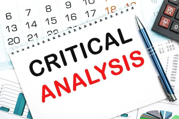Notizbuch mit der textkritischen analyse auf dem bürotisch, dokumenten, taschenrechner, brille und stift