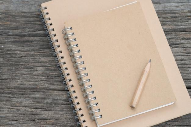 Notizbuch mit einem bleistift auf hölzernem