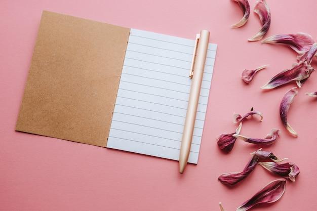 Notizbuch mit einem leeren weißen gestreiften blatt, stift und getrockneten blütenblättern auf mattrosa hintergrund