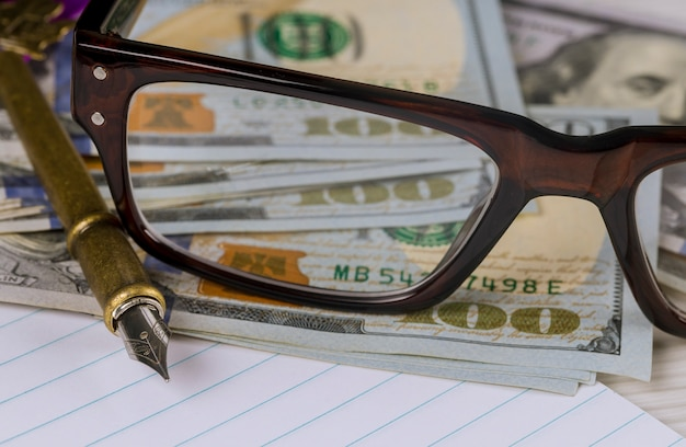Notizbuch mit finanzgeschäftsbuchhaltung der dollar, des stiftes und der gläser