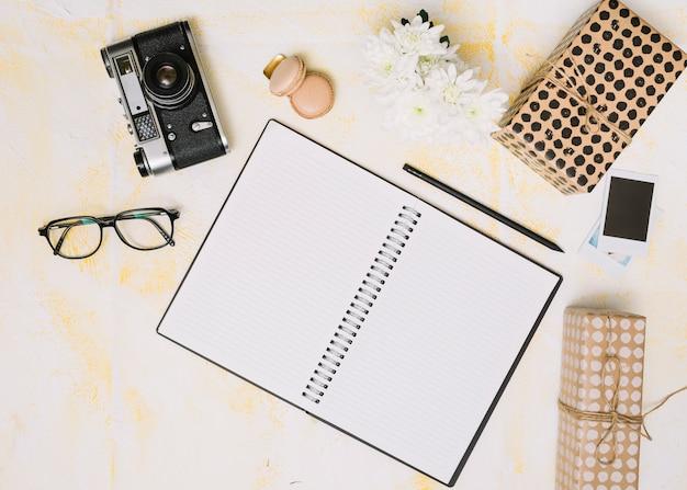 Notizbuch mit geschenkboxen, kamera und blumen auf tabelle