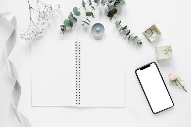 Notizbuch mit hochzeitsverzierungen daneben