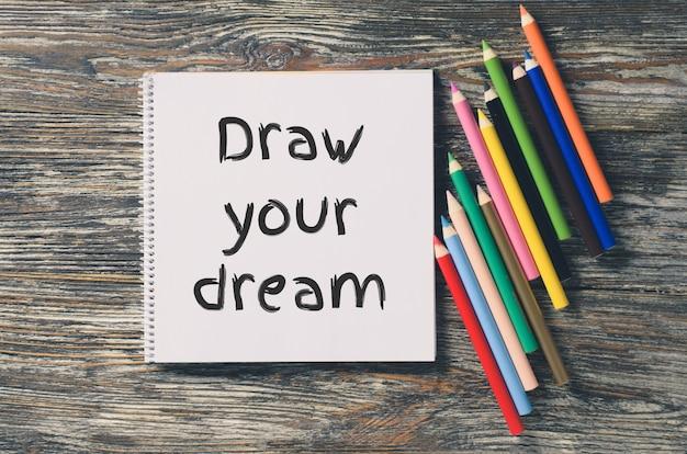 Notizbuch mit inspiration zeichnen sie ihren traum und ein set buntstifte.