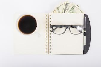 Notizbuch mit Kaffee und Gläsern auf Schreibtisch