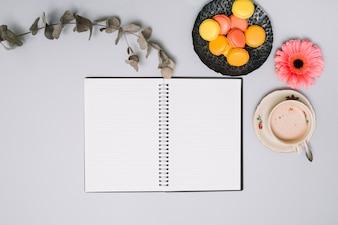 Notizbuch mit Keksen und Blume auf Tabelle
