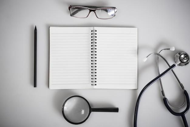 Notizbuch mit leerem spack und medizinischer ausrüstung für medizinischen konzepthintergrund