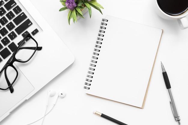 Notizbuch mit leerseite ist auf der weißen schreibtischtabelle mit versorgungen. draufsicht, flach zu legen.