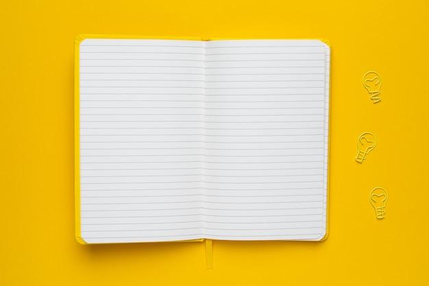 Notizbuch mit leerseiten und glühlampeidee der papierklammer auf gelb