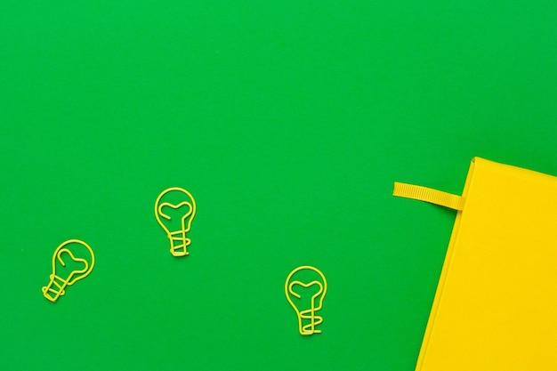Notizbuch mit leerseiten und glühlampeidee der papierklammer auf grün