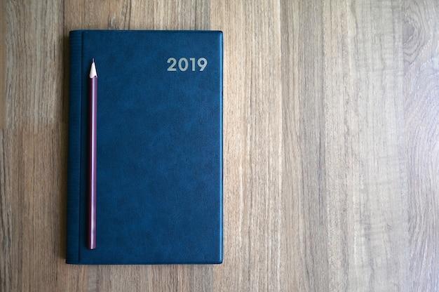 Notizbuch mit nummer 2019 und bleistift auf holztisch mit textfreiraum für text- oder produktanzeige.