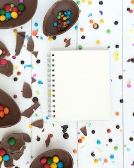 Notizbuch mit offenen schokoladen-ostereiern und -süßigkeiten