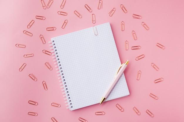 Notizbuch mit pinkfarbener kunststoffabdeckung, stift und büroklammern. rosa hintergrund selektiver fokus