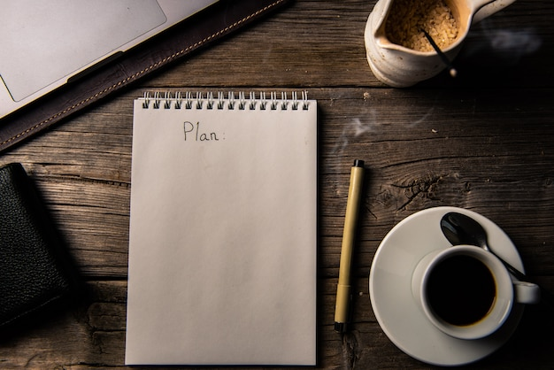 Notizbuch mit planinschrift auf altem holztisch des geschäftsmannes