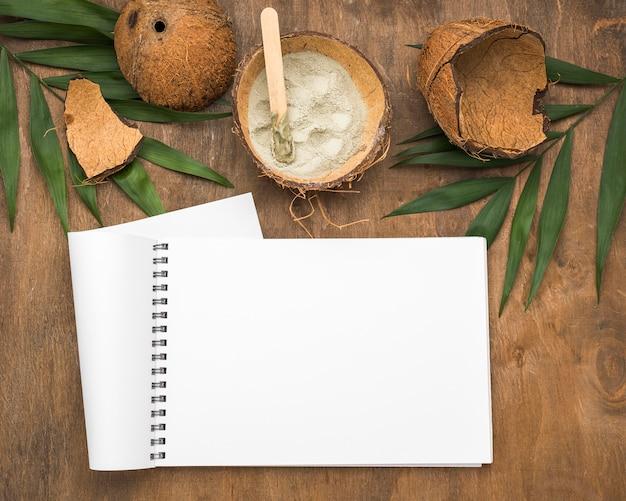Notizbuch mit pulver in kokosnussschale und blättern