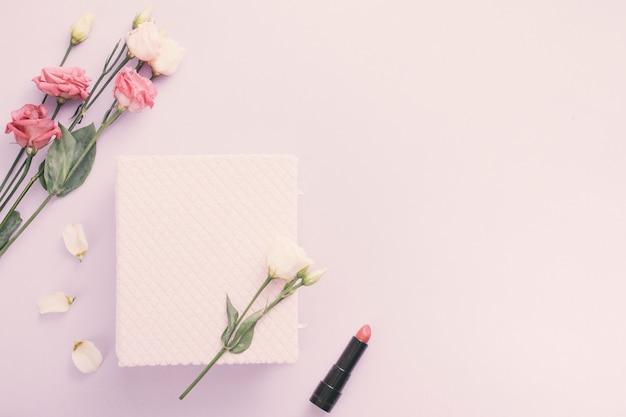 Notizbuch mit rosafarbenen blumen und lippenstift auf tabelle