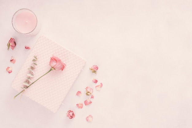 Notizbuch mit rosafarbener blume und kerze