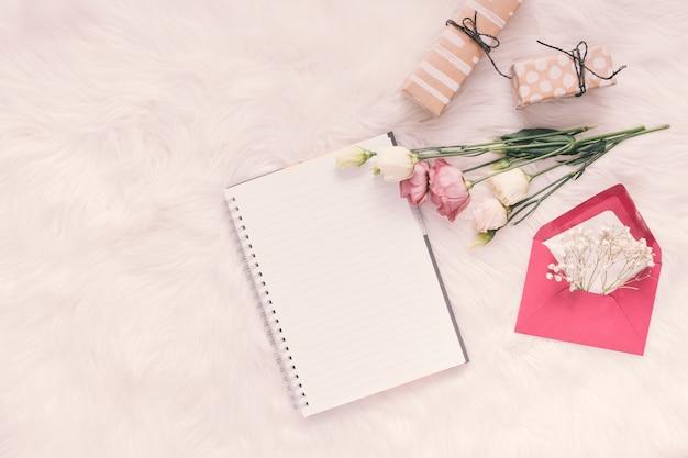 Notizbuch mit rosen, geschenken und umschlag auf heller decke