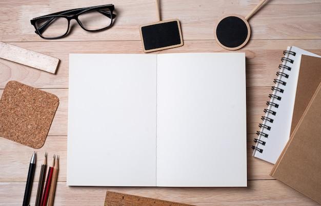Notizbuch mit schulmaterial und tafel auf einem holztisch.