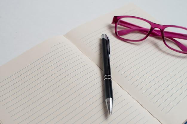 Notizbuch mit schwarzem stift und violetter brille