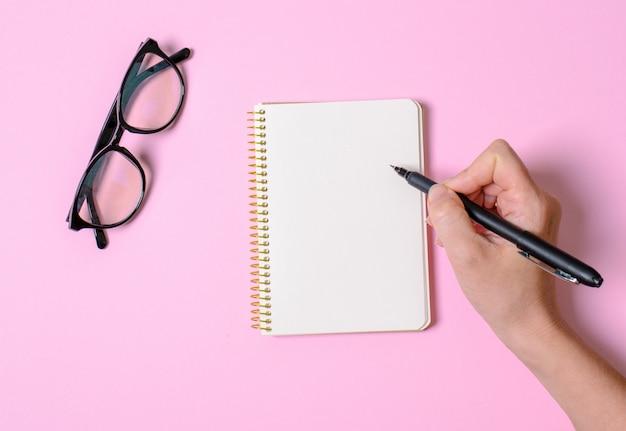 Notizbuch mit spickzettel, hand mit griff, bürobrille. ein ort für text.