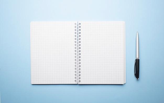 Notizbuch mit stift auf blauer oberfläche draufsicht