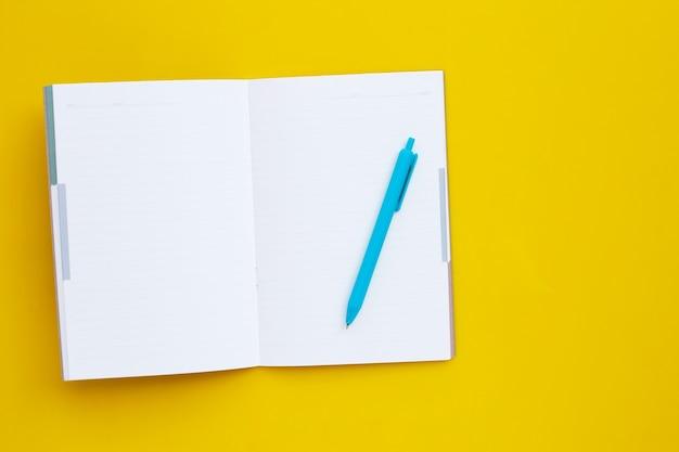 Notizbuch mit stift auf gelber oberfläche