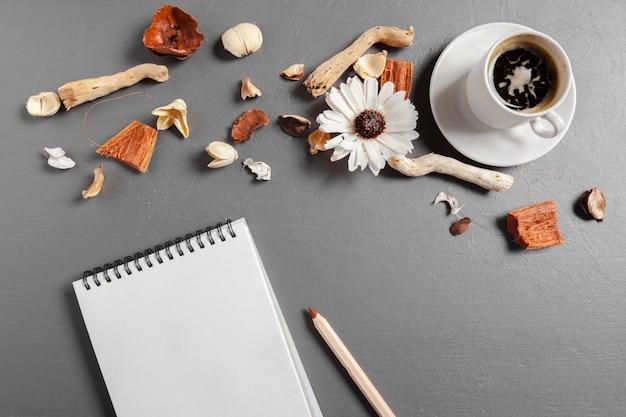 Notizbuch mit stift, kaffee und blume auf tabelle