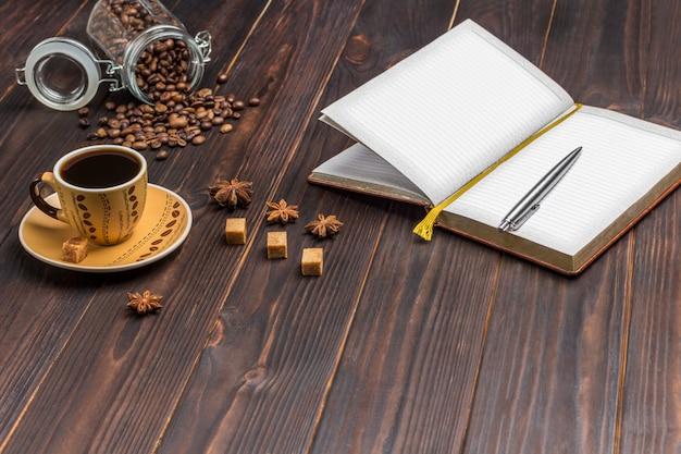 Notizbuch mit stift öffnen. tasse kaffee, kaffeebohnen im glas. auf dem tisch gewürze sternanis und stücke braunen zuckers.