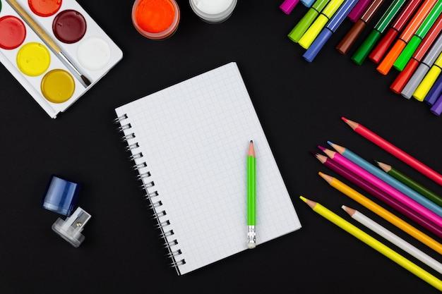 Notizbuch mit stiften und farben auf schwarzem hintergrund