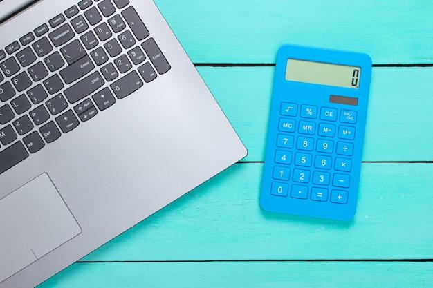 Notizbuch mit taschenrechner auf einem blauen holz.