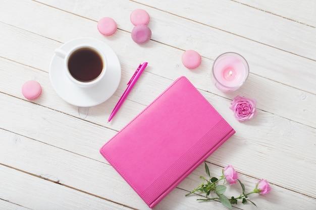 Notizbuch mit tasse kaffee auf weißem holztisch