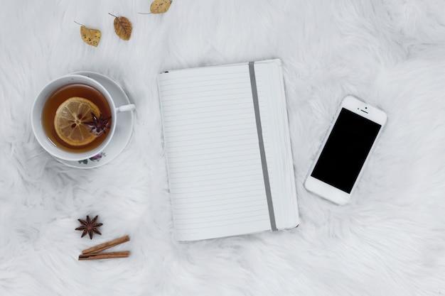 Notizbuch mit teetasse nahe smartpone auf plaid