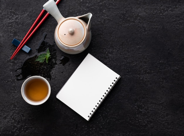 Notizbuch mit teezusammensetzung mit keramischen teetassen und teekanne auf dunklem steinhintergrund mit copyspace