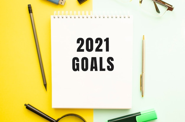 Notizbuch mit text 2021 ziele auf bürotisch mit büromaterial. gelbes farbhintergrundkonzept. unternehmenskonzept.
