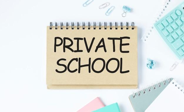 Notizbuch mit text private school blatt weißes papier für notizen, taschenrechner, brille, bleistift, stift
