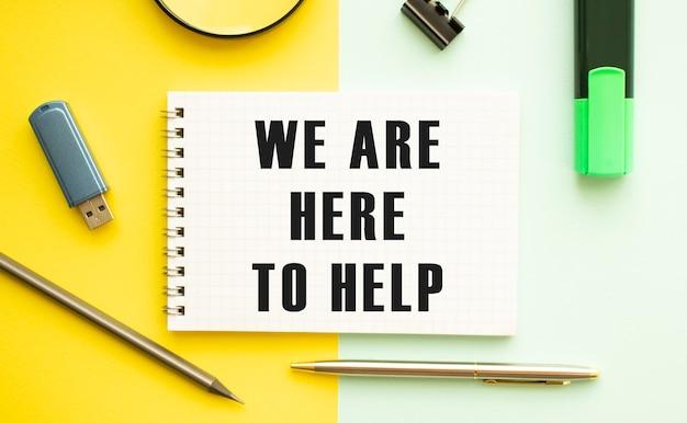 Notizbuch mit text wir sind hier, um auf bürotisch mit büromaterial zu helfen. gelbes farbhintergrundkonzept. unternehmenskonzept.