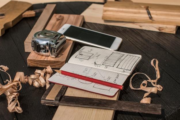 Notizbuch mit zeichnungen, bleistift, maßband, smartphone, quadrat und flugzeug auf einer schwarzen tabelle