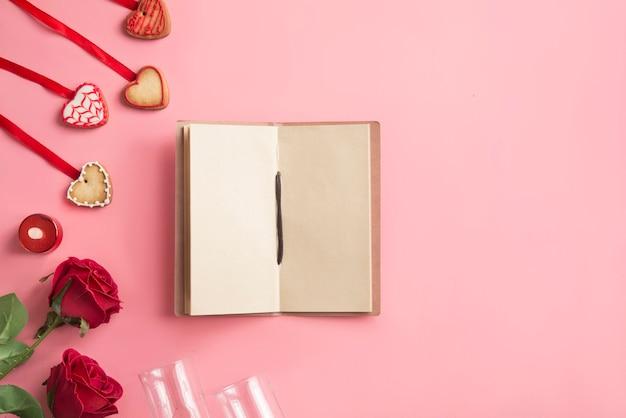Notizbuch mit zwei rosen, zwei gläsern und plätzchen
