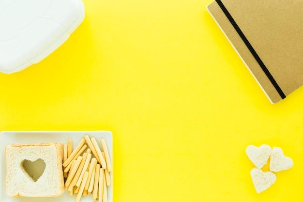 Notizbuch nahe lunchbox und platte mit lebensmittel