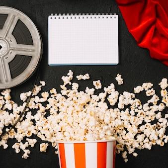 Notizbuch nahe popcorn und filmrolle